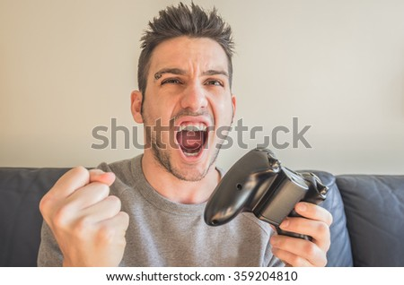 Young man with a joystick for game console - stock photo