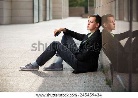 Young man with a mobile phone sitting at the wall - stock photo