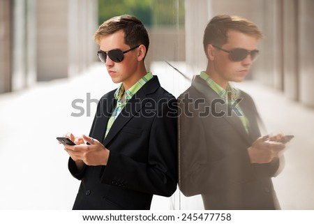 Young man with a mobile phone standing at the wall - stock photo