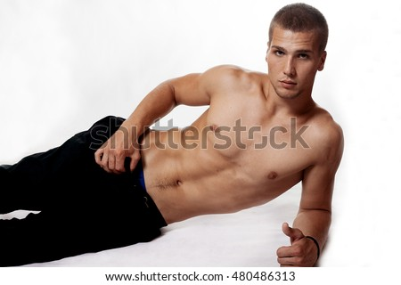 Young man with a naked torso in jeans on a white background