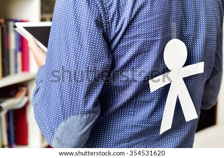 young man with a paper man in his back with for the dia de los inocentes, the innocents day, a feast held in spain, hispanic america and philippines equivalent to april fools day - stock photo