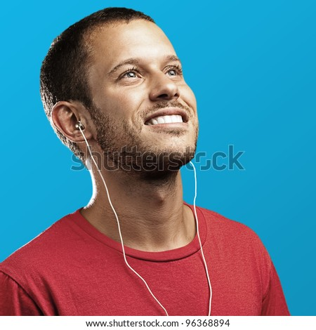 young man with a red shirt on a blue background - stock photo