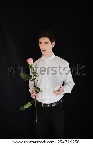 young man with a rose and telephone on the black background - stock photo
