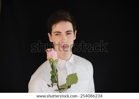 young man with a rose on the black background - stock photo