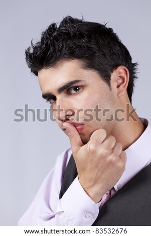 Young man with a sexy look expression (isolated on gray) - stock photo