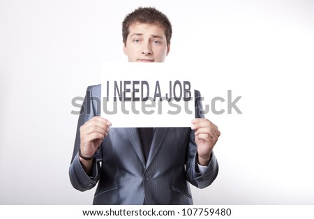 Young man with a sign I need a job. - stock photo