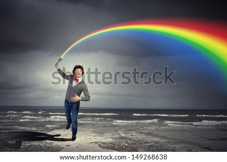 Young man with a splash coloured like a rainbow - stock photo