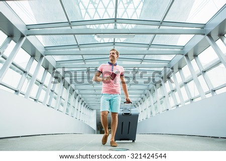 Young man with a suitcase at the airport - stock photo