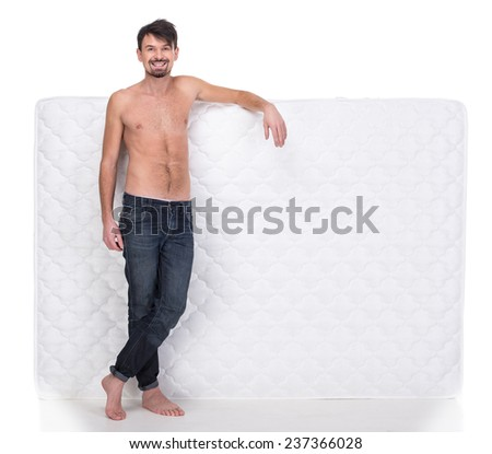 Young man with a white mattress isolated on white background. - stock photo