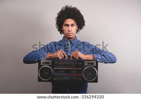 Young man with afro hold old tape recorder - stock photo