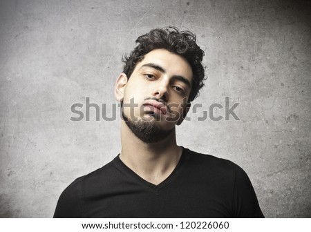Young man with an arrogant face - stock photo