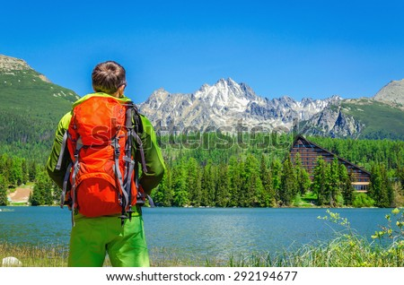 Young man with an orange backpack admire the beauty of a mountain lake, Strbske Pleso, High Tatras, Slovakia