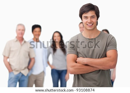 Young man with arms folded and friends behind him against a white background