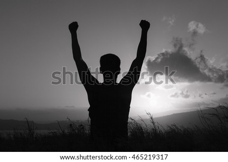 Young man with arms in the air celebrating. People winning feeling happy and free.