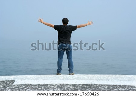 young man with arms open contemplating the ocean in foggy day - stock photo