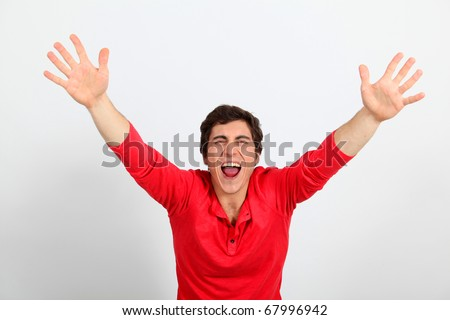 Young man with arms up shouting outloud - stock photo