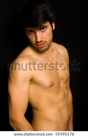 Young man with atletic body on black background