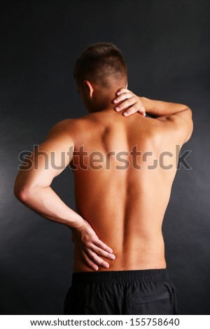 Young man with back pain on grey background - stock photo