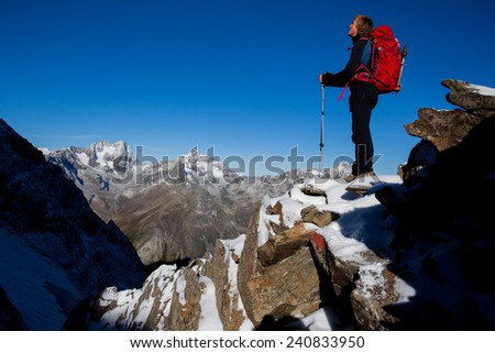 Young man with backpack enjoying the view from a mountain ridge - stock photo