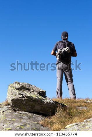 Young man with backpack hiking into the mountains - stock photo