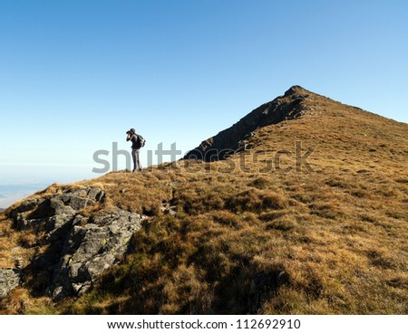 Young man with backpack hiking into the mountains and taking photos from the top - stock photo