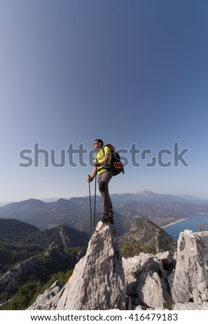 Young man with backpack on a mountain top on a sunny day.