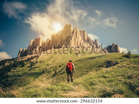 Young Man with backpack relaxing outdoor Travel Lifestyle hiking concept with rocky mountains on background Summer vacations  - stock photo