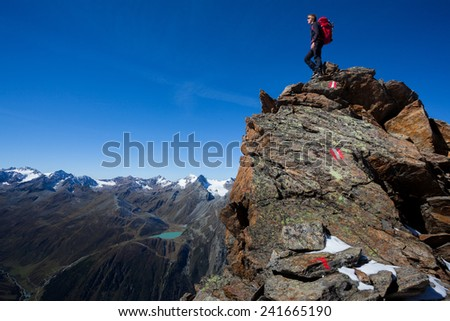 Young man with backpack standing high above alpine valley - stock photo