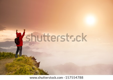 Young man with backpack standing  on top of  mountain watching the sunrise - stock photo