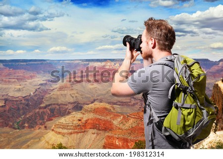 Young man with backpack taking a photo on the top of mountains at Grand Canyon, caucasian - stock photo
