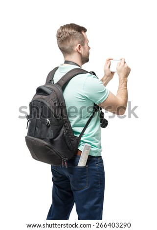 Young man with backpack taking a photo over white background - stock photo