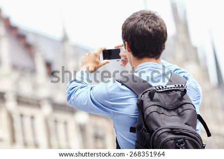 Young man with backpack taking picture with smartphone on city center during vacation - stock photo
