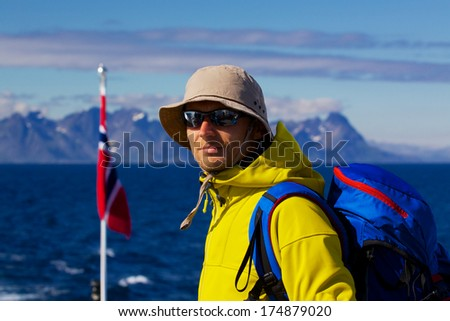 Young man with backpack with panorama of Lofoten islands in Norway in the background