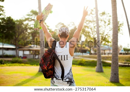 Young Man with bag and cap,Travel Lifestyle concept with city on background.Sunshine portrait of young hipster with board and travel bag,opposite palms.Swag man,hipster man in swag outfit,cool beard - stock photo
