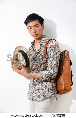 young man with bag,hat standing in studio - stock photo