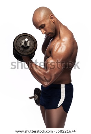 young man with bare chest lifting dumbbells. Fit young man exercising with dumbbells on grey background. image of sweaty bodybuilder.