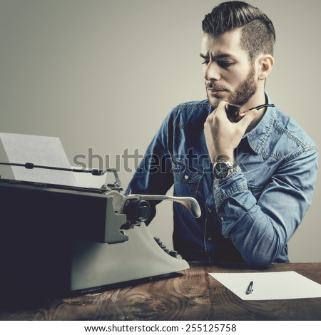 Young man with beard and mustache at the typewriter while smoking his pipe - stock photo