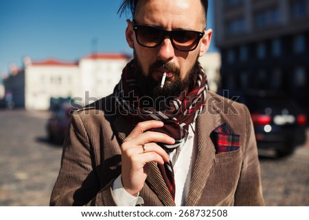 young man with beard and sunglasses posing on the street and Smoking a cigarette