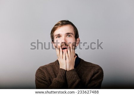 young man with beard in brown sweater in shock