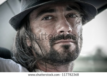 Young man with beard on the back seat of a car with the wind in his hair - stock photo
