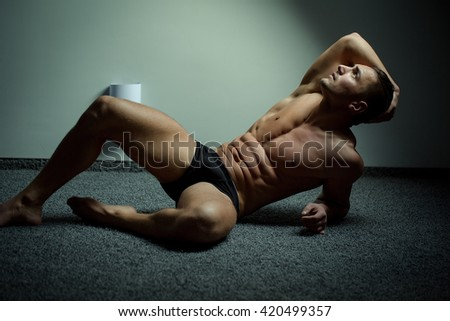 Young man with beautiful muscular torso in underwear lying on floor