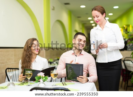 Young man with beautiful smiling girlfriend making order in cafe. Focus on man