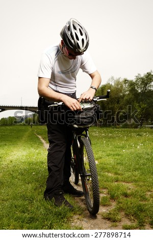 Young man with bicycle enjoying trip near river in city - stock photo
