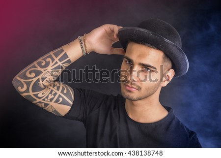Young man with black bowler hat and tattoos - stock photo