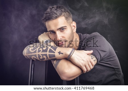 Young man with black t-shirt and tattoos - stock photo