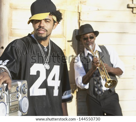 Young man with boom box standing next to senior man with trumpet - stock photo