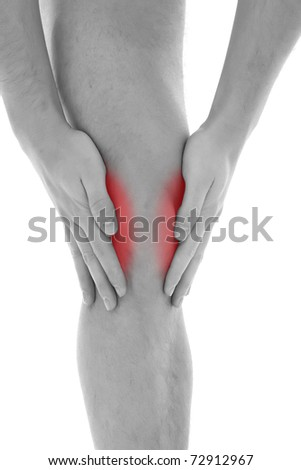 Young man with both palms around knee - stock photo