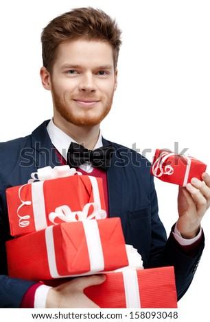 Young man with bow tie carries a lot of different sized presents, isolated on white - stock photo