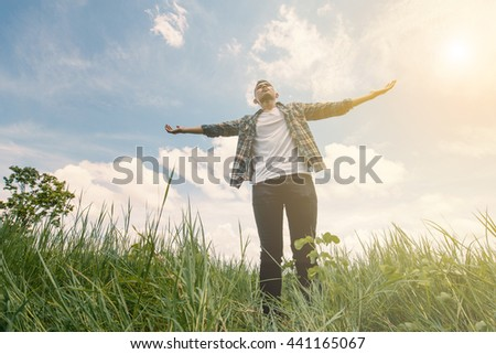 Young man with camera at meadow against sky.Man standing on green grass background
