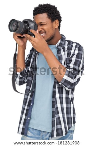 Young man with camera standing over white background